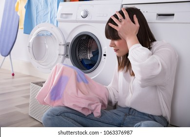 Upset Young Woman Looking At Stained Cloth In Laundry Room