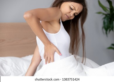 Upset young woman sit in bedroom suffering from backache or discomfort after waking up, hurt girl massage back muscles feel pain sleeping in uncomfortable posture relaxing in inconvenient bed