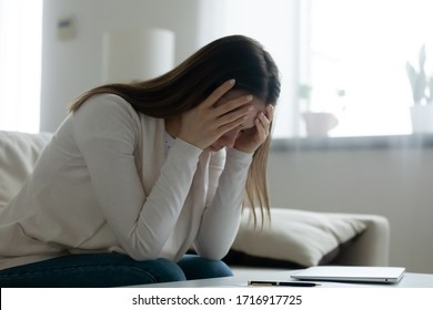 Upset young woman sit on couch at home distressed about breakup or relationships problems, unhappy millennial female lost in thoughts feel lonely or heartbroken frustrated by troubles, grieve or yearn
