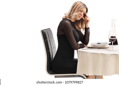 Upset young woman sitting at a restaurant table isolated on white background