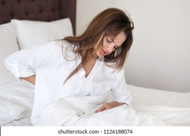 Upset young woman stretching in bed feeling morning discomfort in aching back, low lumbar pain, backache after sleeping on bad mattress in incorrect posture, suffering from painful periods concept