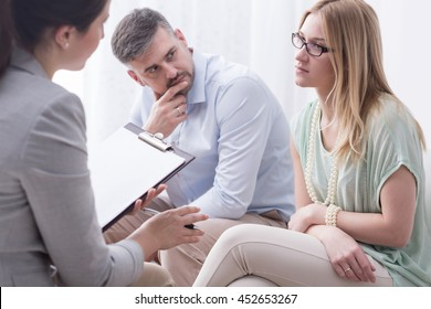 Upset young woman talking to a female psychologist, with her husband aside