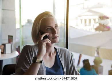 Upset young woman talking on the phone while sitting in cafeteria.