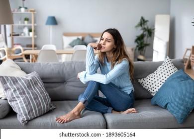 Verärgerte junge Frau, die über Probleme nachdenkt, allein auf dem Sofa zu Hause sitzt, psychologisches Problem.