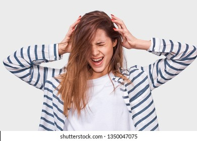 Upset young woman trying comb unruly damaged hair, screaming from pain, discomfort, posing over white background. Pretty business woman dressed in striped shirt suffering from headache. People, health