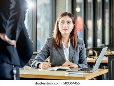 Upsetting face expression of young female employee sitting and writing note on table with laptop in front of angry manager