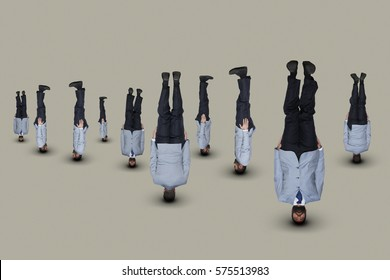 Upside down businessmen in light-blue suits.