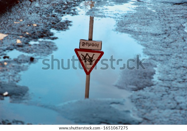 Upside Down and Mirrored Reflection of a School Road Sign in a Puddle After the Rain