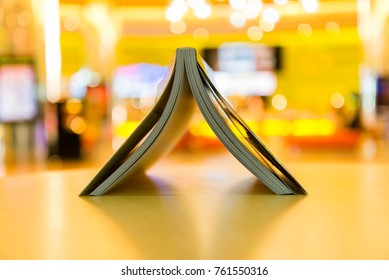 Upside down opened book on blurred warm background