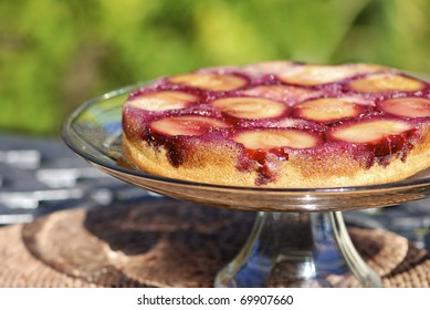 Upside down plum cake on a serving plate