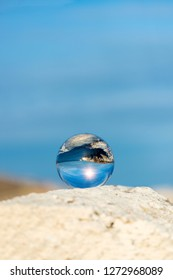 Upside down seascape with blue sky and overgrown with moss rocks - reflection in a lensball - selective focus, space for text