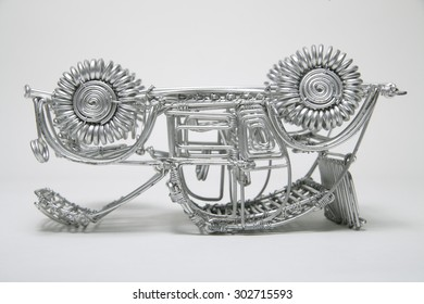 Upside down toy car made of pliable wire against white background,close up