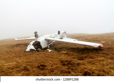 The upside down wreckage of a light aircraft on a high, fog covered mountain
