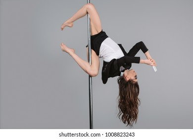 upside down of young businesswoman in eyeglasses using smartphone and exercising with pole on grey