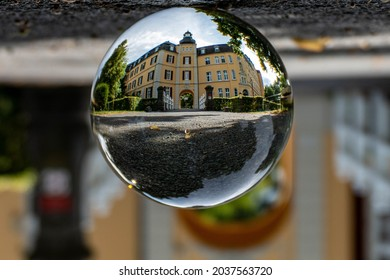 An upside-down closeup shot of a lens ball on the ground reflecting a building in Haus Aspelt - Shutterstock ID 2037563720