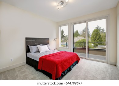 Upstairs bedroom interior with a balcony, minimalistic style: Creamy walls, grey carpet floor and bed with red blanket. Northwest, USA