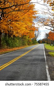 Upstate Fall. Rural street in northern New York lined with bright orange fall trees.