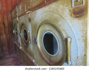 Upstate NY, USA - July 2, 2018: A forgotten laundromat is the home to this row of neglected and rusted out industrial dryers.