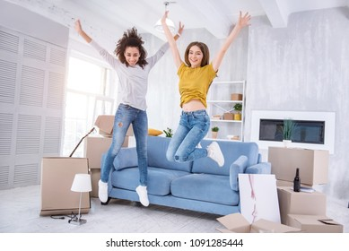 Upsurge of emotions. Pleasant cheerful girls jumping happily in a new apartment while celebrating moving into a new shared flat together