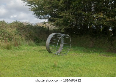 Upturned Metal Livestock Feeder in a Field on a Farm at Simonsbath within Exmoor National Park in Rural Somerset, England, UK