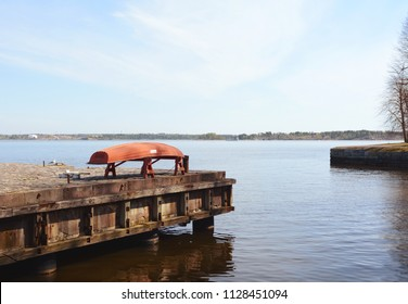 Upturned red boat on a pier above still water on the shore of Suomenlinna sea fortress in Finland