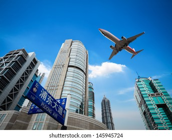 upward view of the airplane with modern financial buildings in shanghai