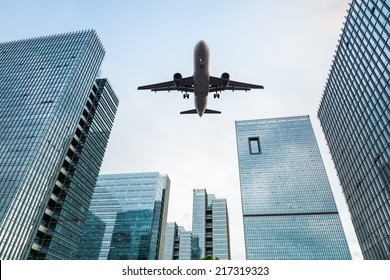 upward view of the airplane with modern office buildings