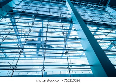 upward view of airport terminal, airplane and glass building with blue tone