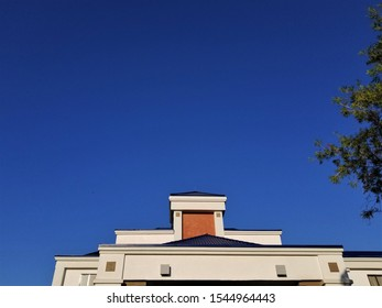 Upward View of a Building's Roofline Against a Deep Blue Sky