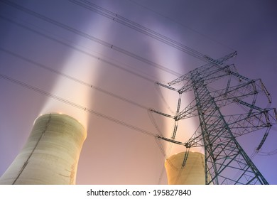 upward view of the cooling towers and high voltage power transmission tower at night