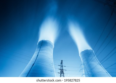 upward view of the cooling towers in a power plant at night