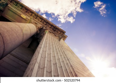 Upward view of a court house with impressive pillars. Morning sun shining down creating a beautiful lens flare. Architectural, construction, law, education and career concept