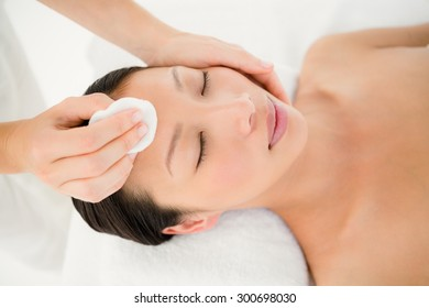 Upward view of hands cleaning woman face with cotton swabs at spa center