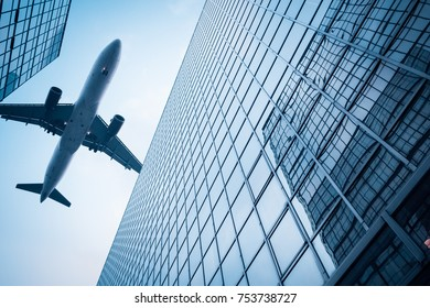 upward view of modern glass skyscraper and airplane