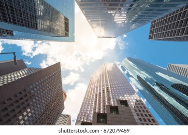 Upward view of skyscrapers against a cloud blue sky in the business district area of downtown Houston, Texas, US.