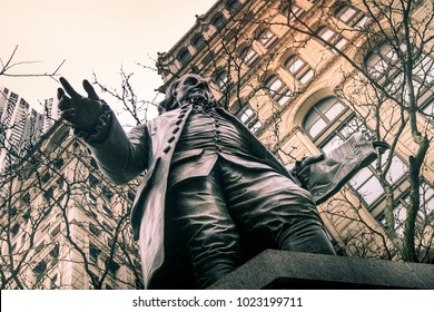 Upward view of a statue of Benjamin Franklin with tree branches and buildings on background.