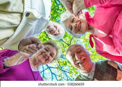 Upward view of two elder couples smiling to the camera. Happiness and retirement concept.