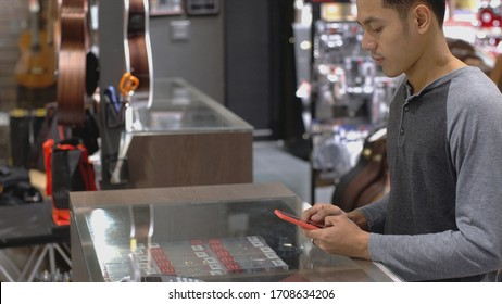 An upwardly mobile Asian Muslim man using a mobile phone - smartwatch to pay for a product at a sale terminal with nfc identification payment for verification and authentication