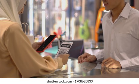 An upwardly mobile Asian Muslim woman using a mobile phone - smartwatch to pay for a product at a sale terminal with nfc identification payment for verification and authentication