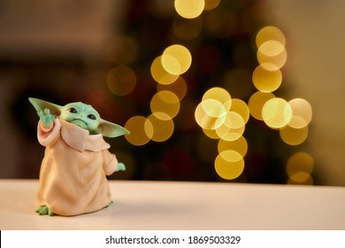 Uralsk, Kazakhstan - Dec 2020. Baby Yoda an action figures stands on white table. Blurred background. High quality photo