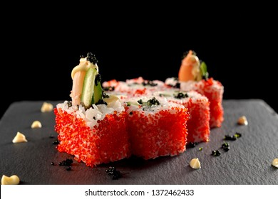 Uramaki sushi rolls covered with red tobiko roe, filled with shrimp, cucumber. Sushi look like volcano, topped with sauce and black caviar. Served on black stone plate.