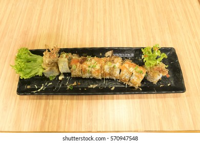Uramakizushi rolls, a Japanese cuisine with filling in the center surrounded by nori, then a layer of rice with outer coating of roe. The slices of rolls in rectangle plate on wooden table background.