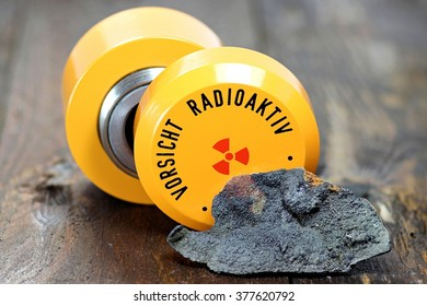 uraninite with storage container for radioactive materials (translation: caution - radioactive)