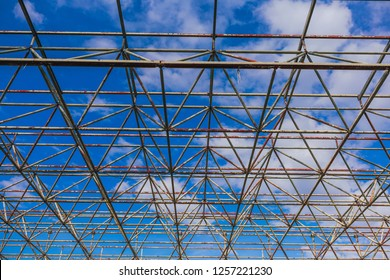 Urban abstract texture background. Point of view looking up in blue sky through old rusty geometric diagonal metal constructions of abandoned building. Horizontal color photography.