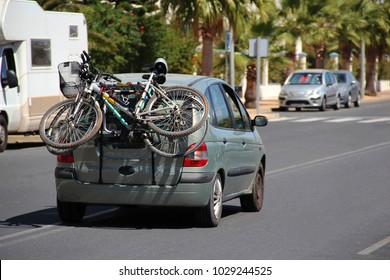 Urban active leisure: two bicycles are attached to the rear to a small car traveling on the highway on a bright, sunny summer day. Concept: movement and sport