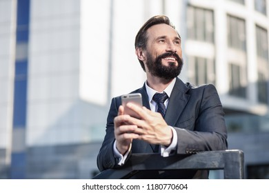 Urban architecture. Waist up of a cheerful handsome businessman holdign his phone while smiling