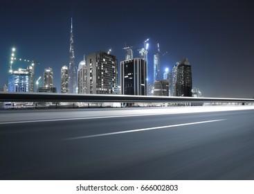 Urban asphalt road with dubai skyline background at night