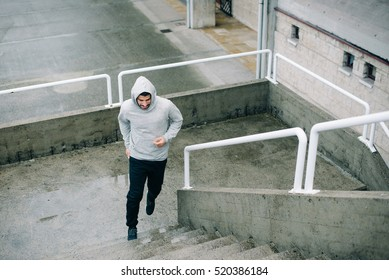 Urban athlete running upstairs. Sporty man working out outside and climbing stairs in rainy winter.