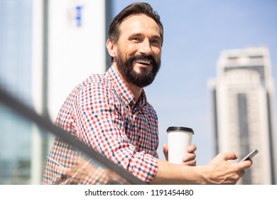 Urban background. Joyful handsome man drinking coffee while standing in urban settings