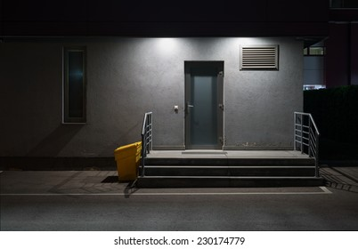 Urban background. Wall and door of the building at night.